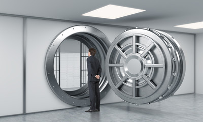 young man standing in front of a big unlocked round metal safe i