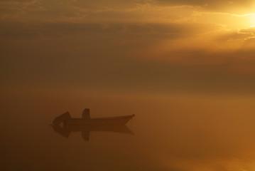 Boat in foggy sunrise