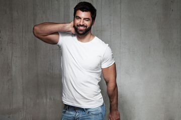 Smiling winking man in a white T-shirt and jeans