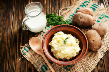 mashed boiled potato with herbs. milk and spices on a wooden background