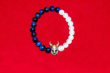 Viking figure blue and white bead men bracelet isolated on red background