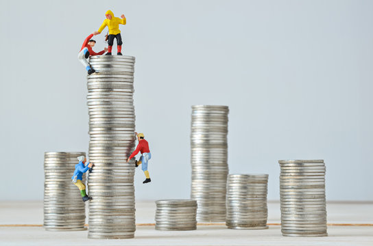 Miniature climbers team climbing on stack of coins