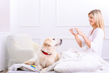 Caring woman lying on bed with her dog