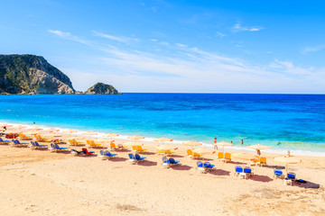 Fototapete - Sunbeds and umbrellas on beautiful Petani beach, Kefalonia island, Greece