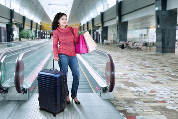 Pretty indian woman standing in airport hall