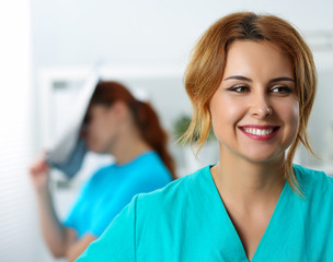 Beautiful female medicine doctor laughing on her colleague