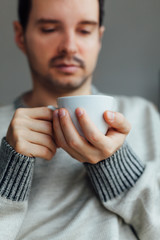 Man warms his hands with a cup of hot tea