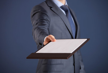 Businessman holding a clipboard with empty sheet of paper