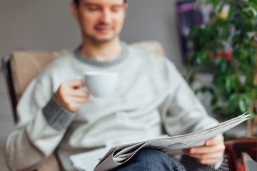 Man sitting and reading newspapers with a cup of tea