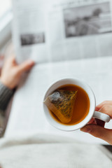 Closeup of man holding cup of tea and reading the newspapers
