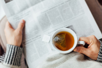 Man holding a cup of tea and reading newspapers