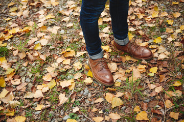 Man's boots on autumnal leaves