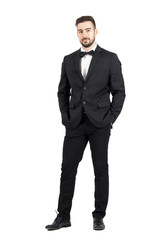 Wealthy confident relaxed young man in tuxedo looking at camera with hands in pockets. Full body length portrait isolated over white studio background.