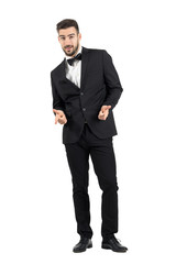 Happy laughing young luxurious man in tuxedo pointing at camera. Full body length portrait isolated over white studio background.