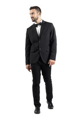 Young beaded man in tuxedo with bow tie walking towards the camera looking away. Full body length portrait isolated over white studio background.