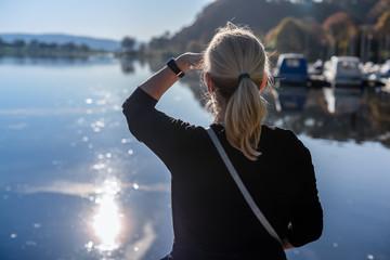 Eine Frau sieht auf einen See.
