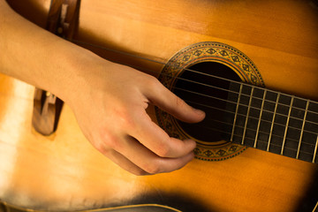 Young guy playing on guitar. Hand and guitar close-up.Soft and blur conception