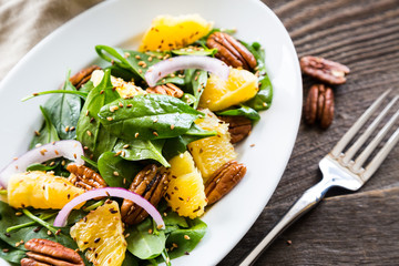 Salad with fresh spinach, oranges and pecan