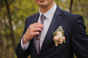 man on his wedding day in suit with plugged Rose