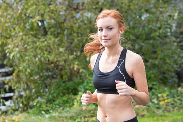 redhead woman running outsdie on a trail