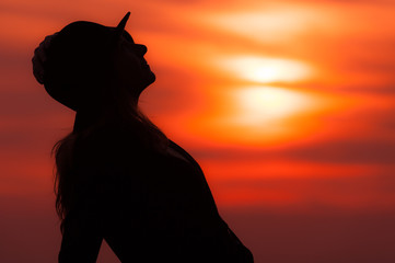 Silhouette of woman at sunset with red sky