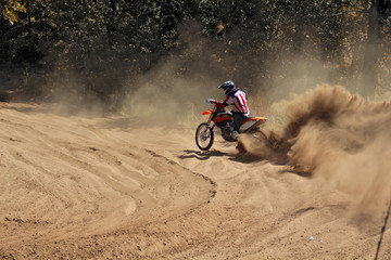 Motocross racer moves along sandy parapet turning track per motorcycle large plume of sand