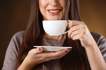 Woman holds cup of coffee and plate in hands, close up