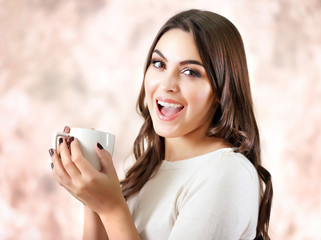 Portrait of smiling pretty woman with cup of coffee on pink blurred background