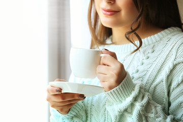 Woman holds cup of coffee in hands, close up