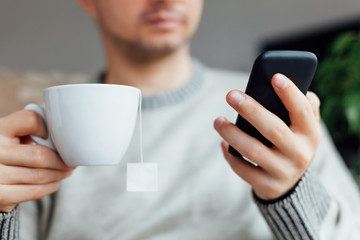 Man with a cup of tea and mobile phone