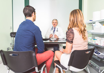 Couple speaking with doctor