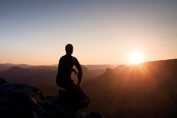 Young man in black sportswear sit on cliff edge and look into daybreak at horizon over misty valley
