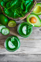 Green smoothie on rustic wooden background