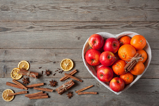 Apples and tangerines with cinnamon on a wooden background
