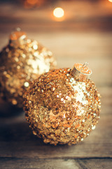 Golden christmas ornaments on rustic background