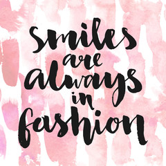 Smiles are always in fashion. Inspirational quote handwritten with black ink and brush, custom lettering for posters, t-shirts and cards. Vector calligraphy on pink watercolor strokes background