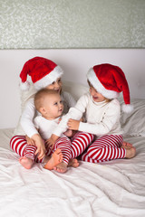funny kids in their pajamas and Christmas caps on the bed
