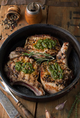 Grilled pork chop with spices in a frying pan