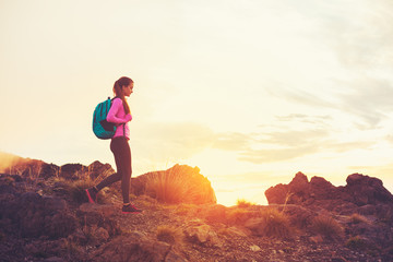 Woman Hiking in the Mountains at Sunset