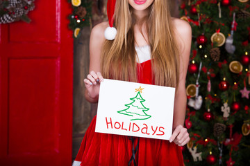 Woman in red dress with holidays picture over christmas tree background. Christmas, holiday and people concept