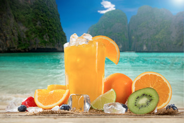 Fresh Fruits on the beach at a deck in front of an tropical islands. Assorted tropical fruits, orange, kiwi, lime, strawberries and blueberries and orange fresh juice with ice.