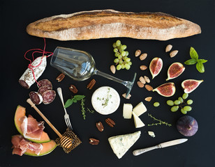 Wine and snack set. Baguette, glass of white, figs, grapes, nuts, cheese variety, meat appetizers, herbs on black grunge background, top view