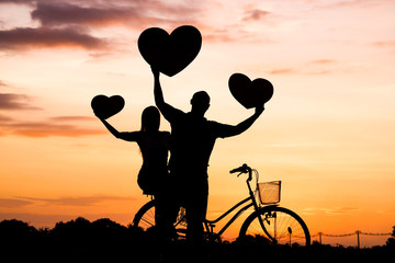 Silhouette of a man and a woman riding a bicycle together and holding big hearts
