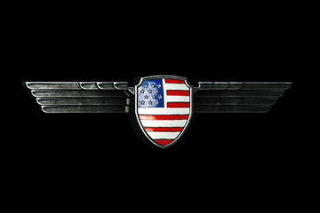 USA flag in metal wings frame isolated on black background.