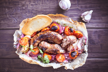 Sausages with onion and tomatoes on old wooden surface