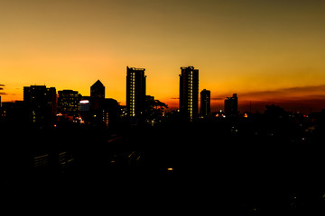 Silhouette of Bangkok cityscape at sunset.