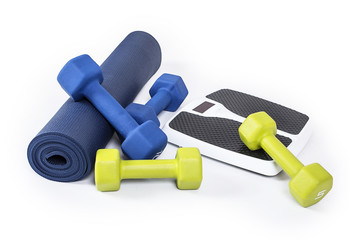 Fitness and weight loss equipment isolated on a white background. A yoga mat, dumbbell weights and a weight scale all together