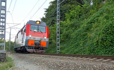 Локомотив везет состав по однопутной железнодорожной ветке