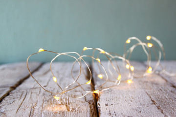 selective focus image of Christmas warm gold garland lights on wooden rustic background