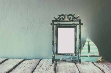 low key image of old victorian steel blue blank frame with fairy garland lights and wooden sailing boat on wooden table. vintage filtered image